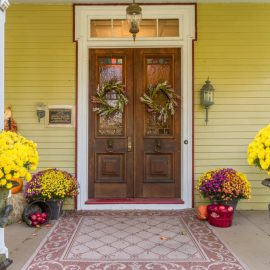 Two pots full of yellow flowers in an entryway