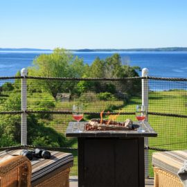Two chairs and a fire pit on a deck overlooking a bay