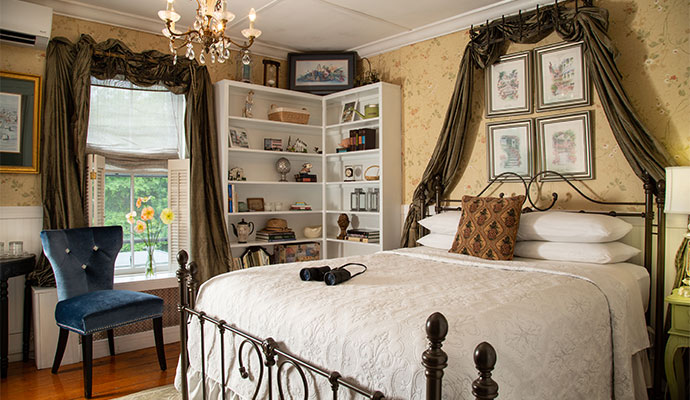 A room with a queen bed and window are framed with yards of silk spilling from window boxes
