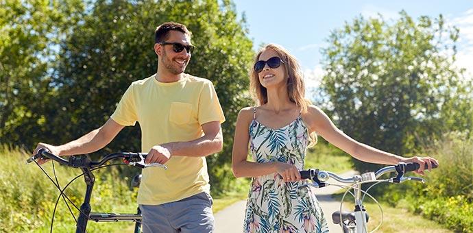 Man and woman smiling while walking bikes
