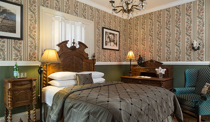 A room with an antique double bed and rich European appointments