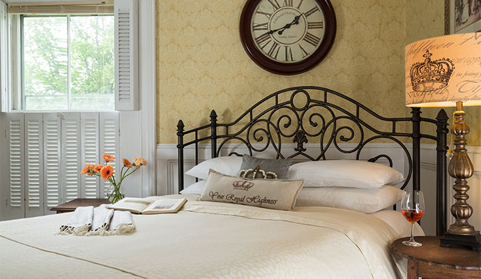 Queen bed in a room with a large clock and a side table with a lamp