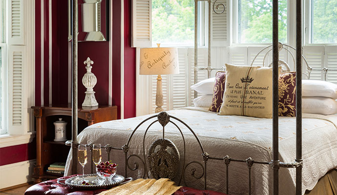 Queen bed in an elegant room with burgundy walls