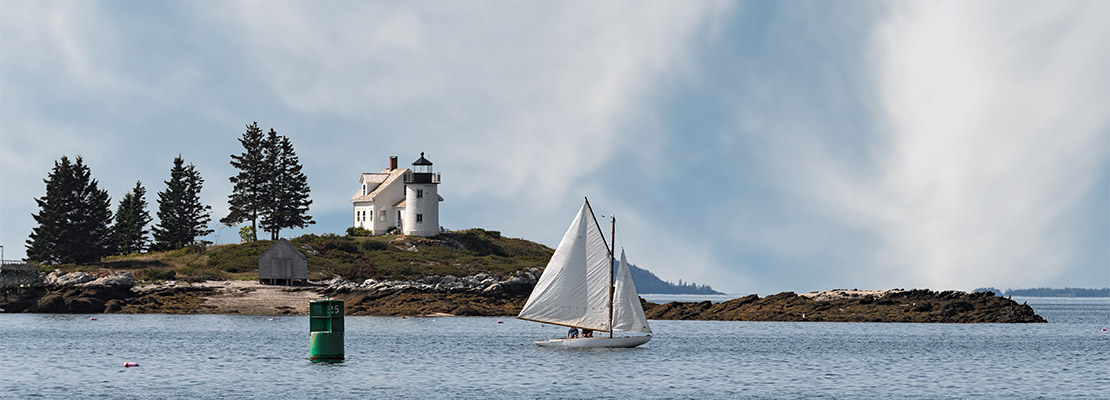 Pumpkin island lighthouse and a sailboat in a bay
