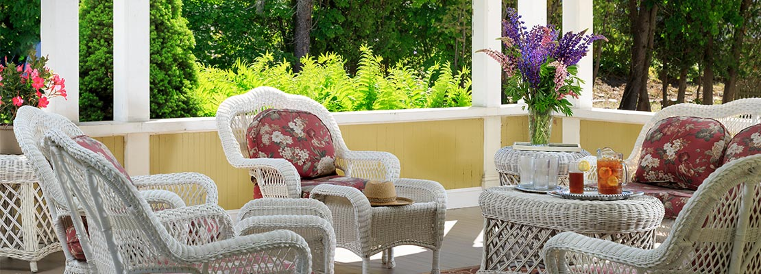 Front porch with white wicker chairs and a table with iced tea