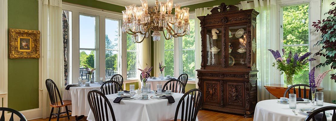 Dining room with a chandelier over a table and large windows with natural light