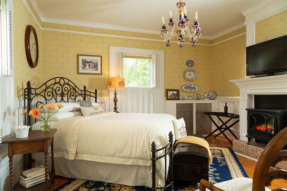 Queen bed in a room with yellow wallpaper and a blue rug