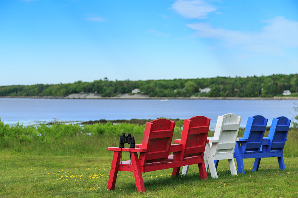 Red, white and blue chairs on a grassy shoreline
