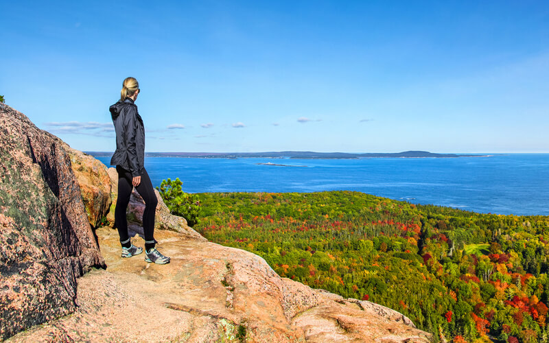 Woman on top of mountain at Acadia National Par with views of treetops and ocean