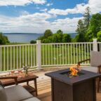 Fire pit on private deck overlooking an expansive lawn and the Maine coast