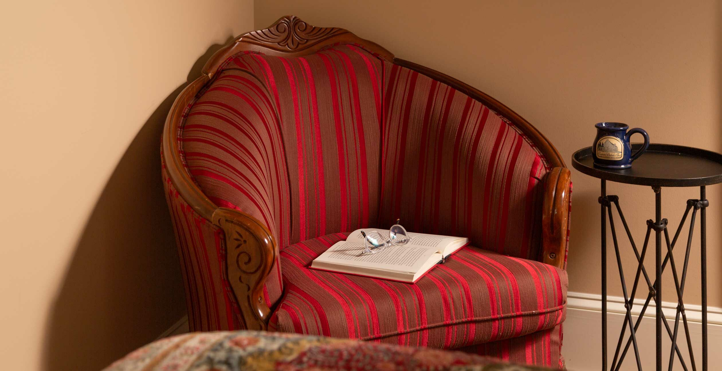 Red arm chair with a coffee cup on a small table