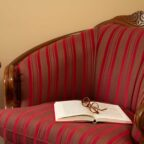 Red arm chair with a coffee cup and red flowers on a small table