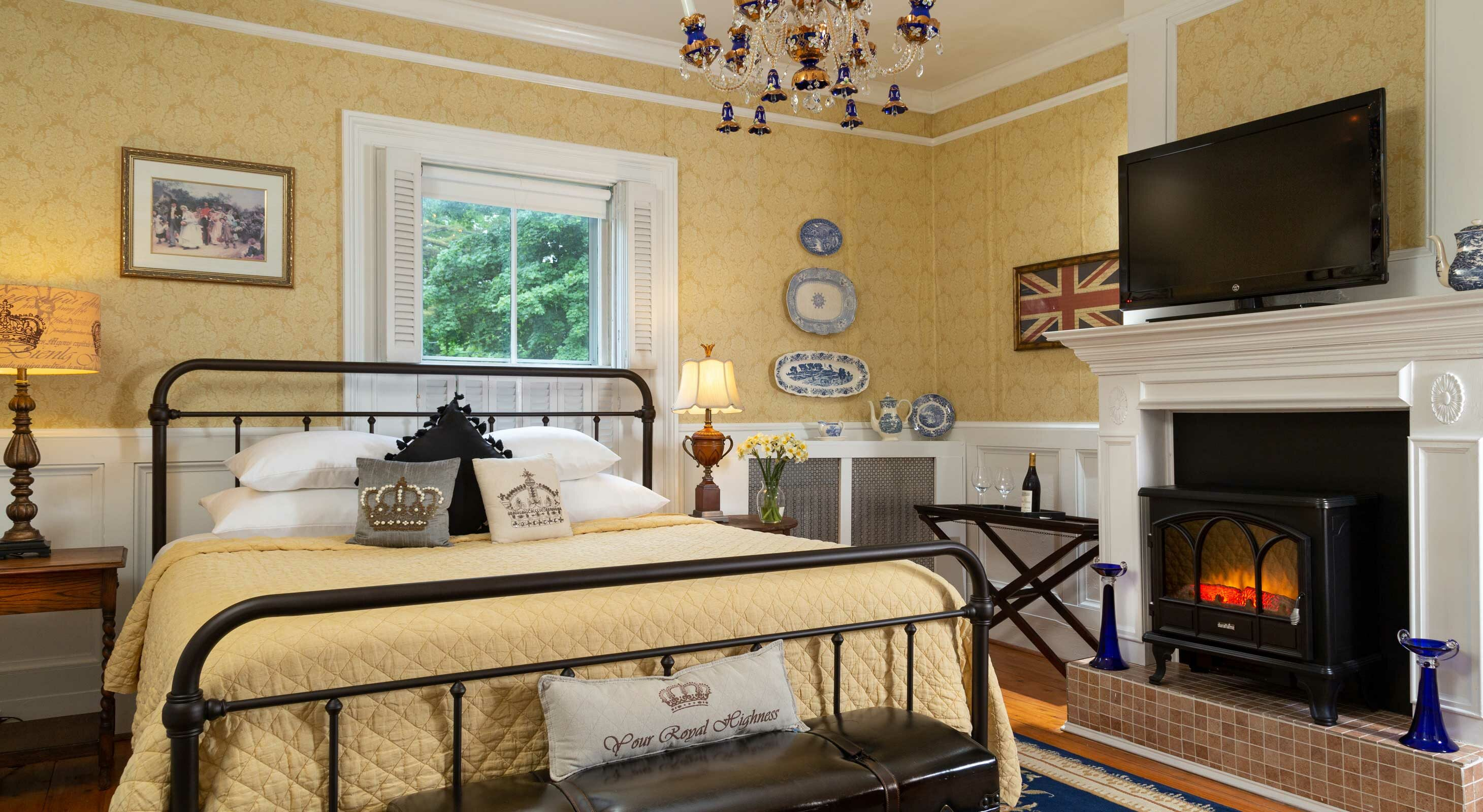 King bed in a room with a blue rug, hardwood floors, and fireplace