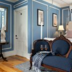 Queen bed in a room with a chair and hallway