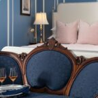 Queen bed in a room with a chair and table with two glasses of champagne