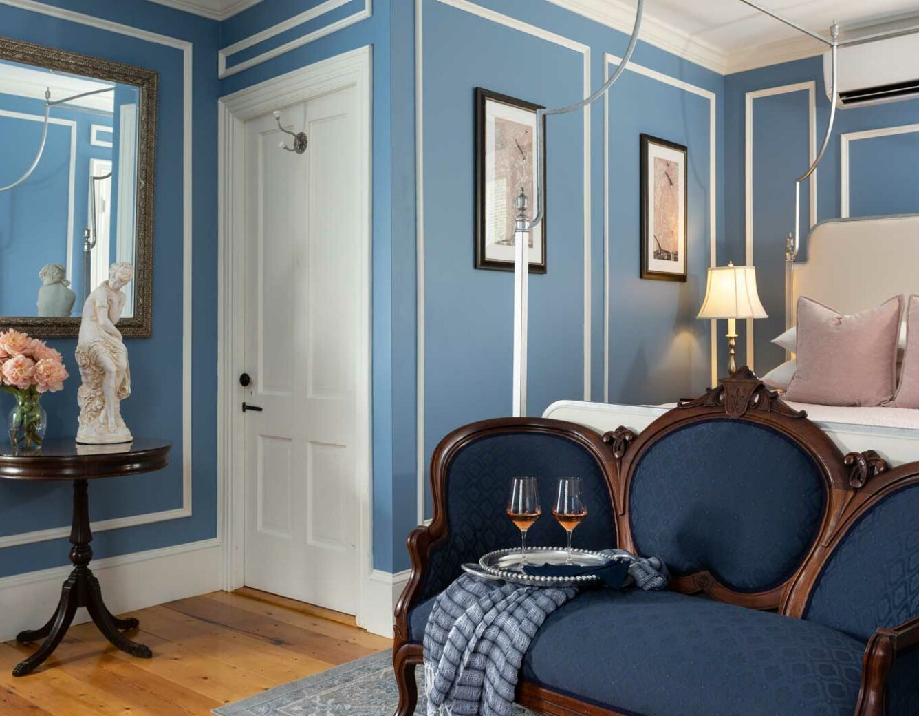 Queen bed in a room with a chair and table