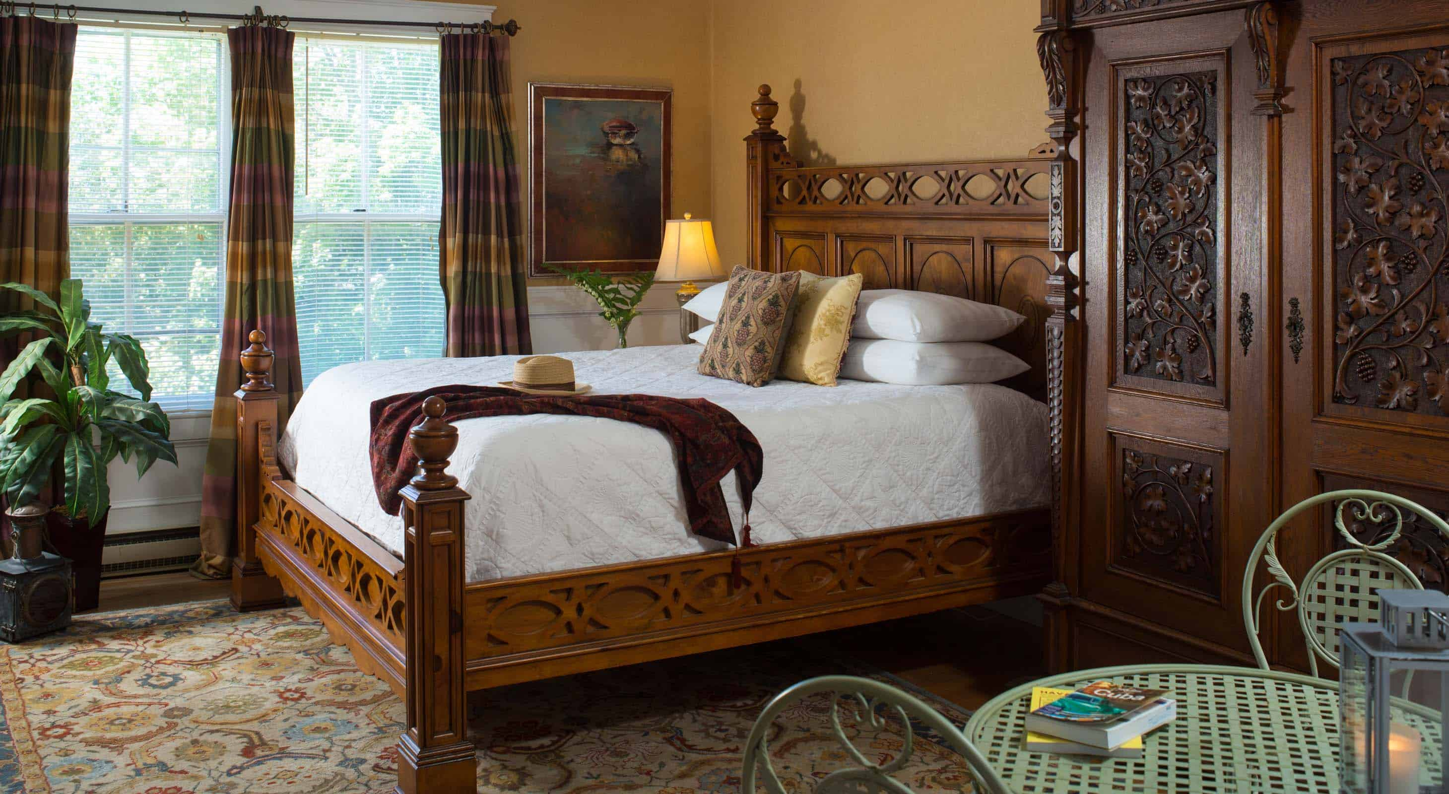 King size bed in a room with a large wardrobe and two windows