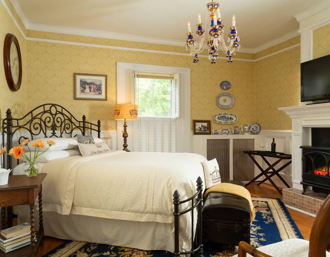 Queen bed in a room with a blue rug, hardwood floors, and fireplace