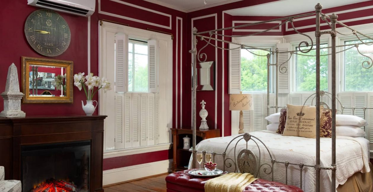 Four-poster queen bed in a room with burgundy painted walls and a fireplace