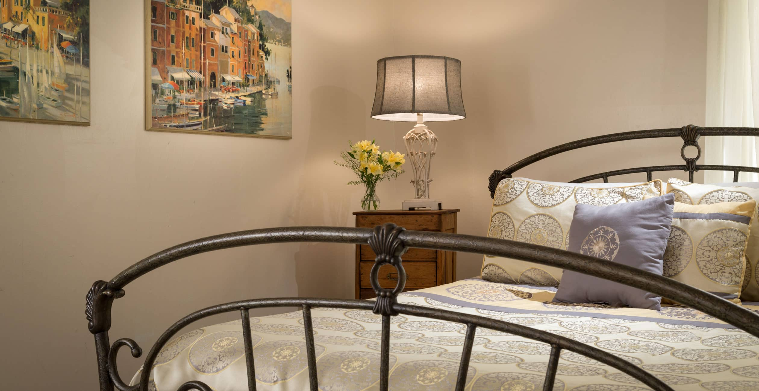 Queen bed with a lamp on an end table