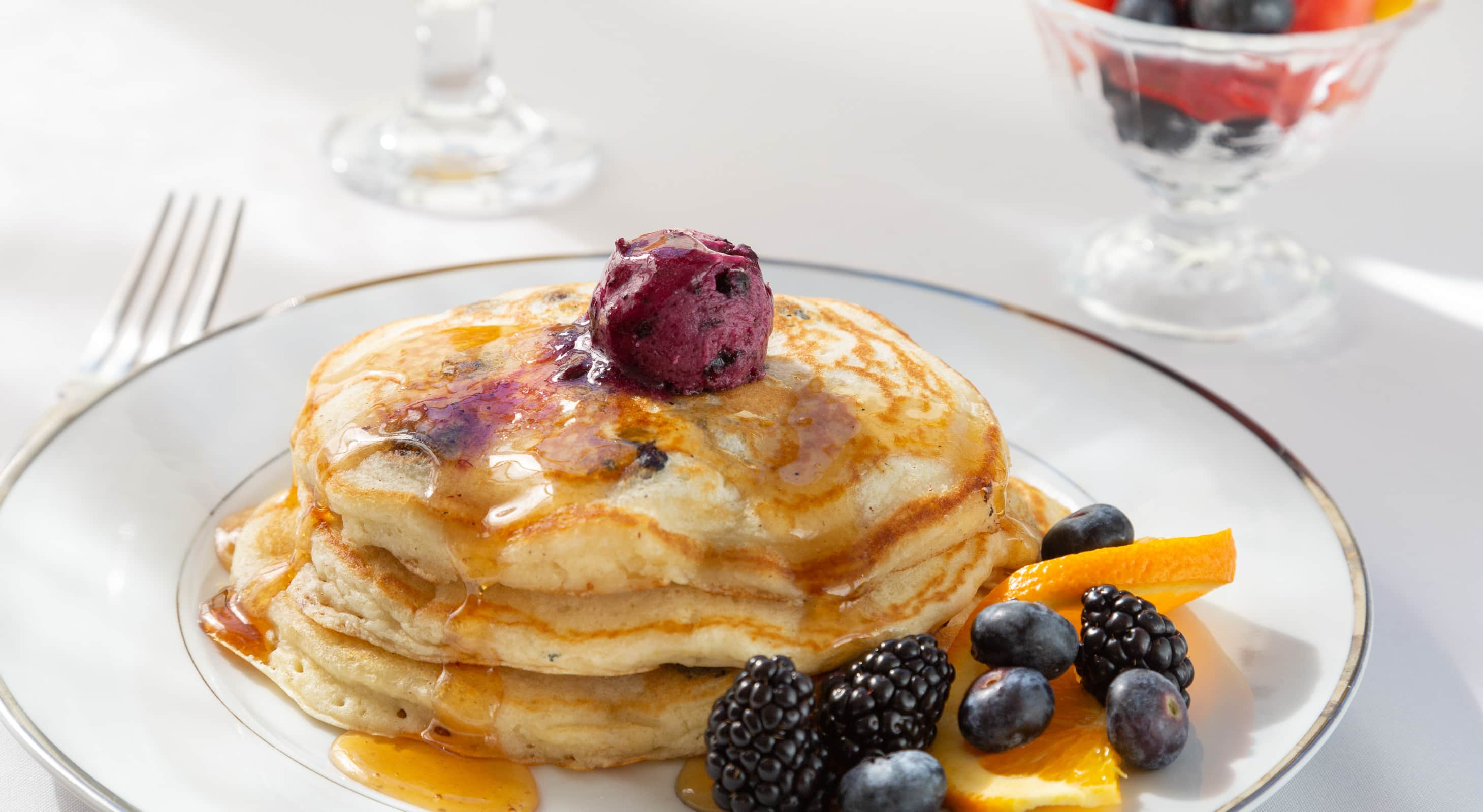 A stack of breakfast pancakes served with fresh fruit
