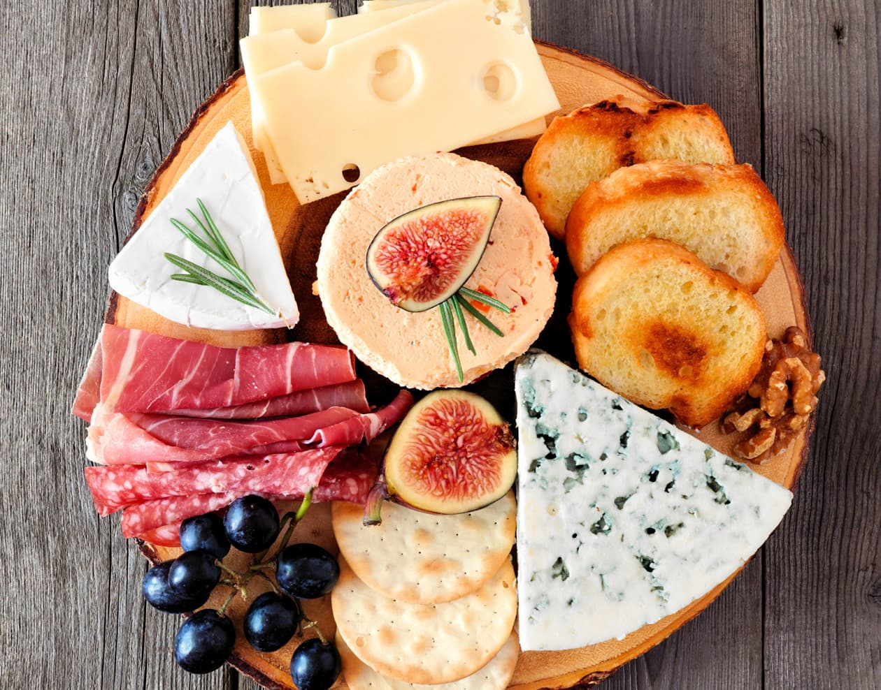 a selection of meats and cheeses on a board