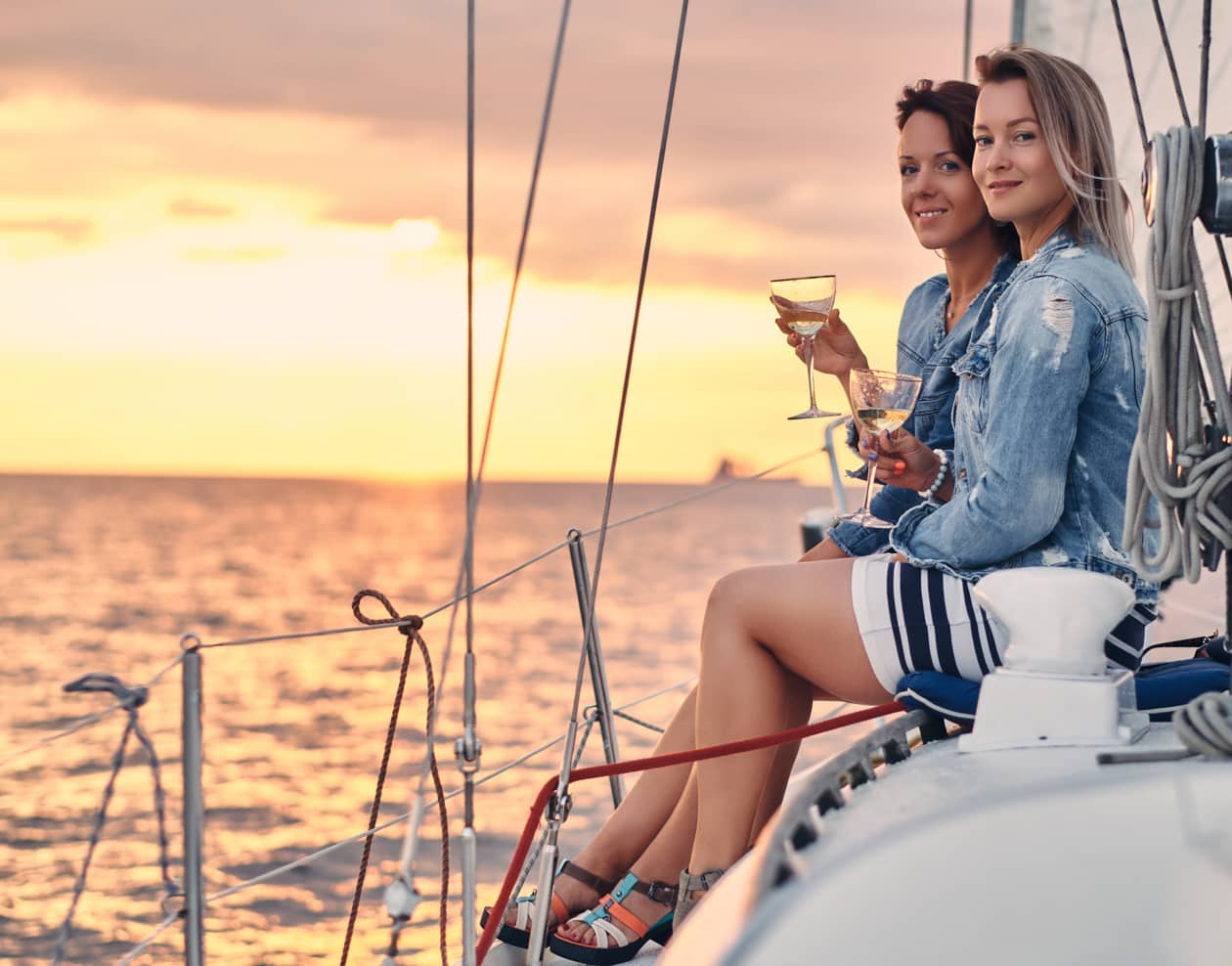 two friends on a sailboat drinking wine