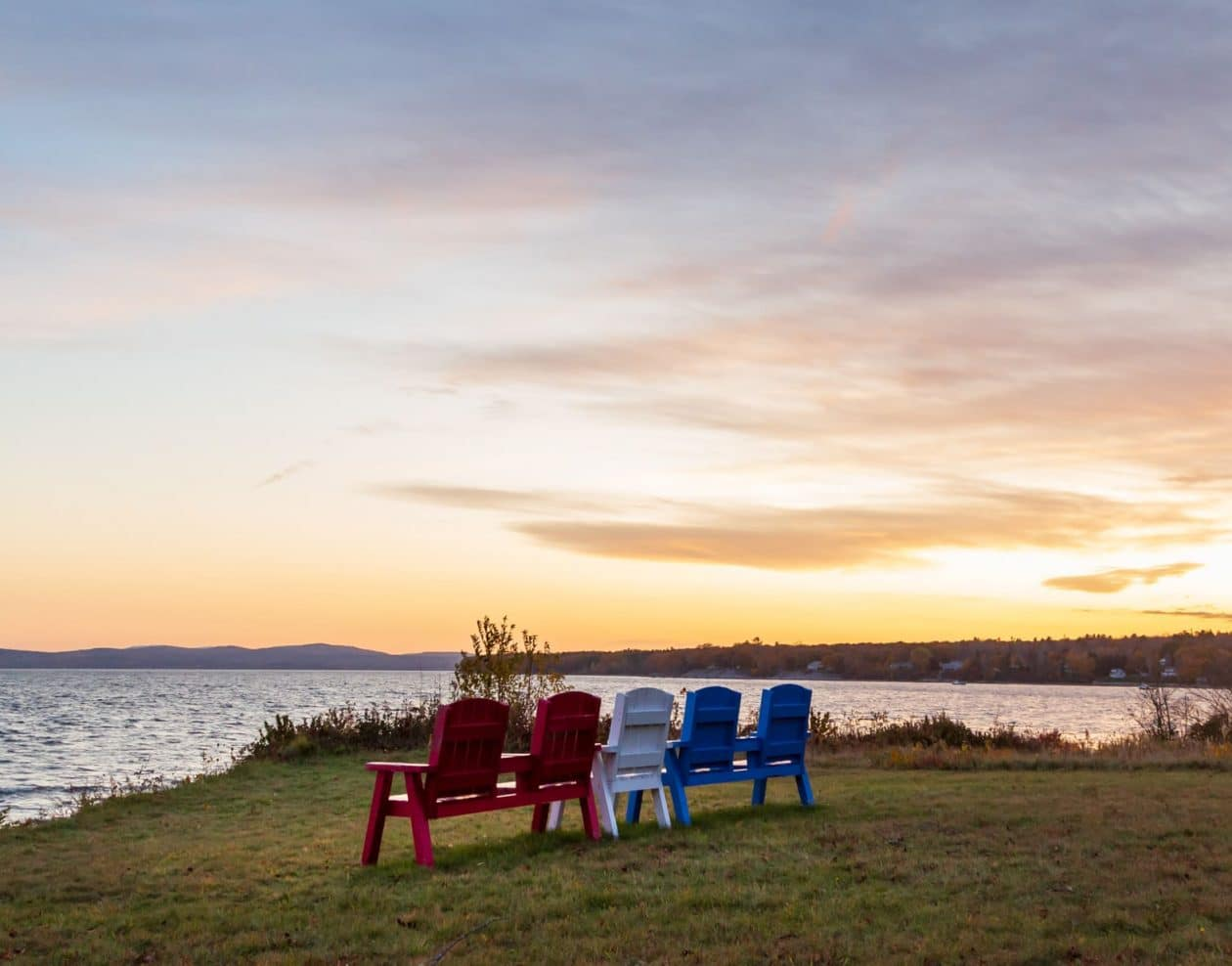 Chairs placed on the shoreline as the sun sets over the Maine coast