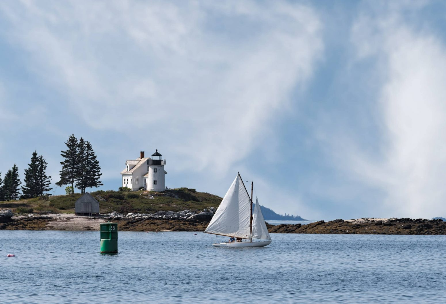 A light house on Pumpkin Island with a small sailboat in the foreground