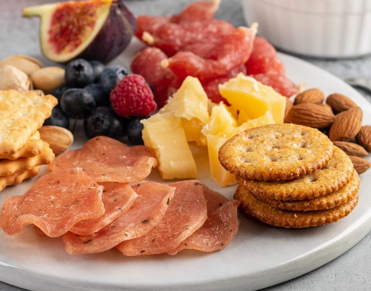 A lunch of crackers, cheese, and fruit