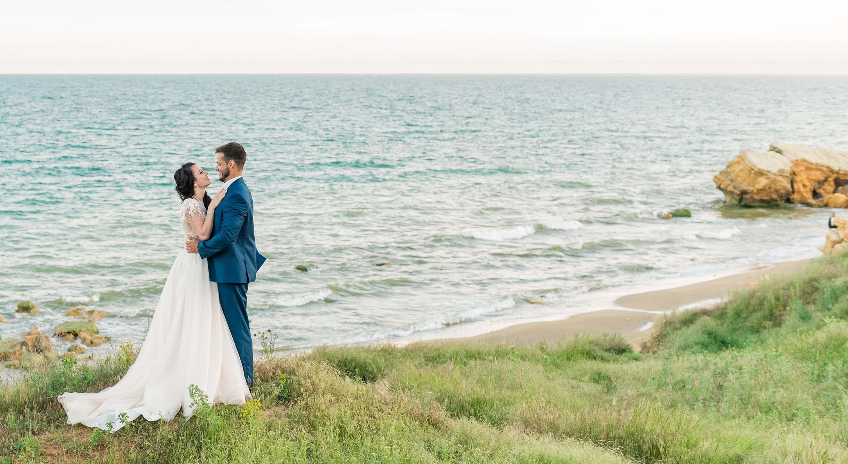 Bride and groom standing at the ocean edge during their Maine elopement