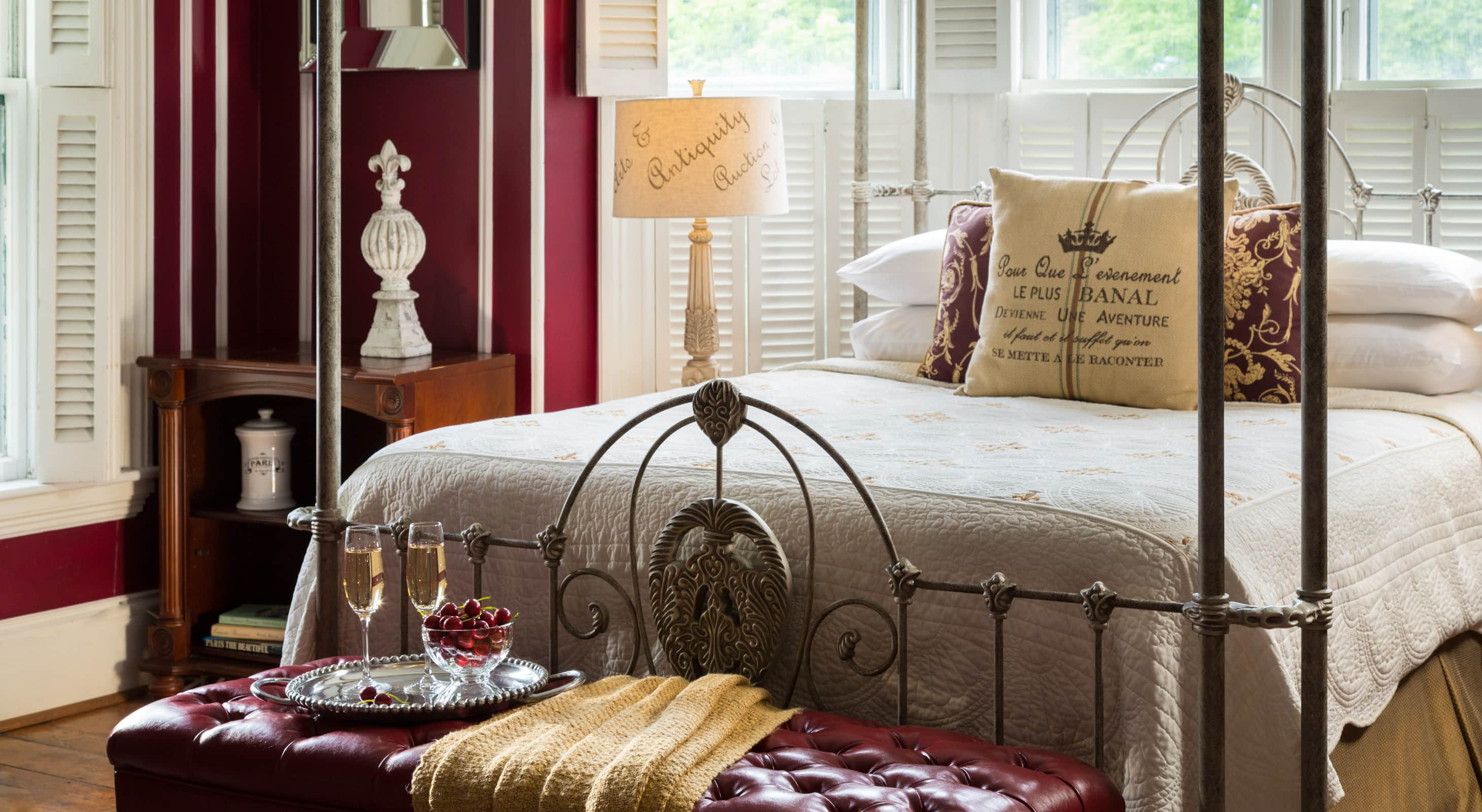 Four-poster queen bed with a reading lamp and a trunk at the foot of the bed