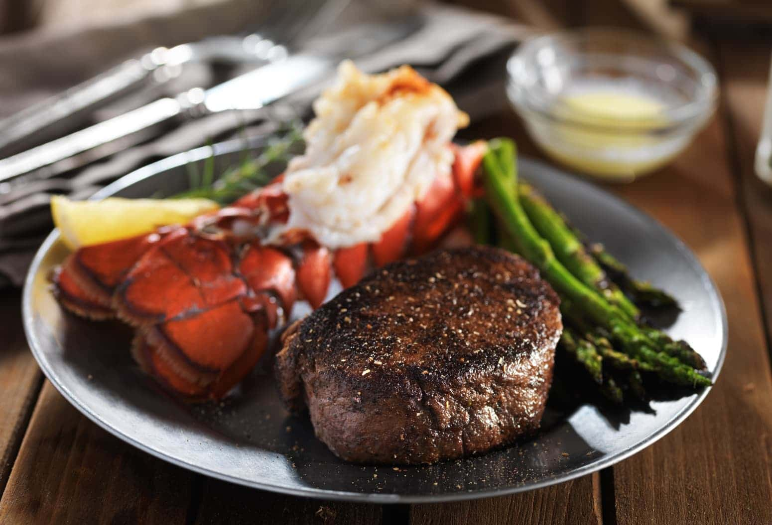 Steak and lobster served with butter and asparagus