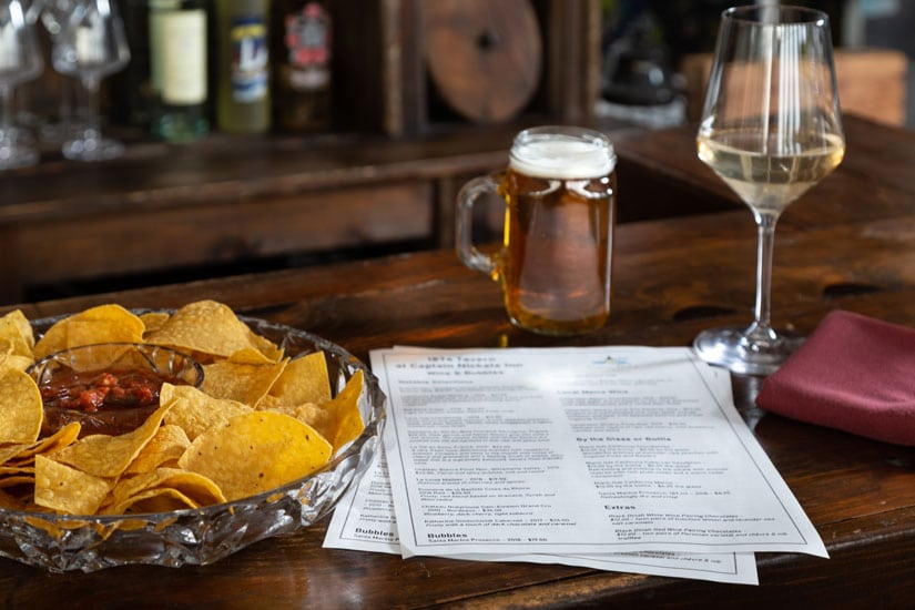 Generous bowl of chips with salsa next to Tavern menus on the bar top. A mug of cold beer and class of wine in the background.