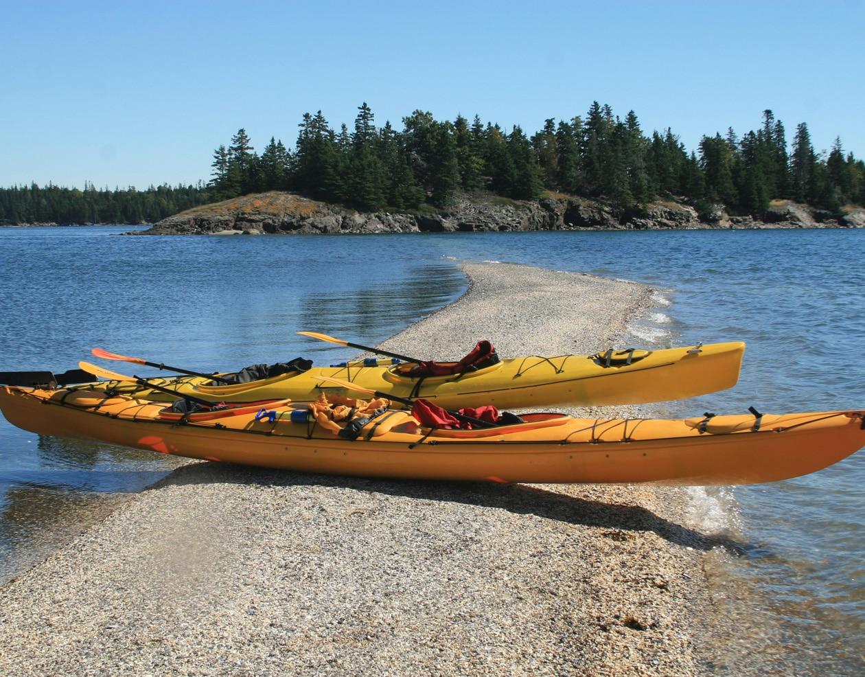 Two yellow kayaks on a sandbar