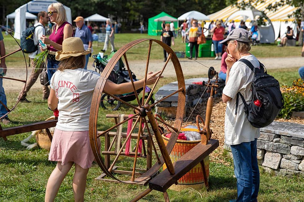 Common Ground Country Fair attendees and spinning wheel